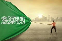 Arabian person dragging flag of Saudi Arabia Royalty Free Stock Image