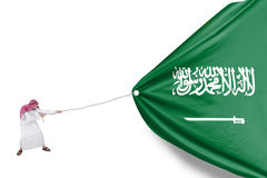 Arabian person pulls Saudi Arabia flag. Image of Arabian person wearing islamic clothes and pulling Saudi Arabia flag in the studio Royalty Free Stock Images