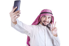 Arabian person taking selfie photo. Young Arabian person taking selfie picture with a smartphone in the studio, isolated on white background Royalty Free Stock Image