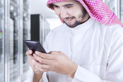 Arabian person uses cellphone in server room. Image of Arabian businessman wearing islamic clothes and using smartphone in the server room Royalty Free Stock Photos