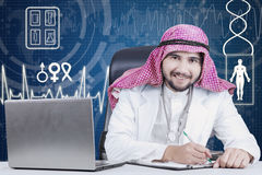 Arabian physician smiling at the camera. Picture of male Arabian physician working clipboard and laptop computer on the table, smiling at the camera Royalty Free Stock Photo