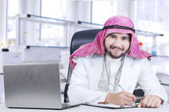 Arabian physician working in the hospital. Photo of a young Arabian physician working in the hospital with clipboard and laptop Royalty Free Stock Photos
