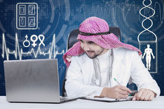 Arabian physician working with laptop. Picture of Arabian physician working on the table while looking at the laptop screen with futuristic screen background Royalty Free Stock Images