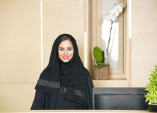 Arabian Receptionist helping a customer on the front desk Stock Images