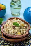 Arabian salad with couscous tabbouleh. Arabian salad with couscous and vegetables tabbouleh on blue background royalty free stock photo
