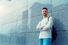 Arabian student with backpack standing by the wall outside. Young man waiting for groupmates. royalty free stock photos