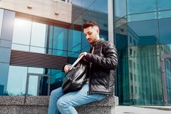 Arabian student takes his copybooks out of backpack outside. Young man sitting by modern university. Arabian student takes his copybooks out of backpack outside Royalty Free Stock Images