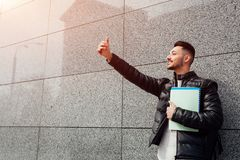 Arabian student takes selfie on smartphone outside. Happy guy looks at phone by wall after classes waiting for friends. stock photo