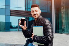 Arabian student using smartphone outside. Happy guy shows phone and hold copybooks outside after classes royalty free stock photography
