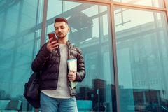 Arabian student using smartphone outside. Serious guy looks at phone in front of modern building after classes. Happy arabian student using smartphone outside royalty free stock image