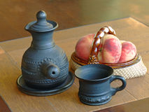 Arabian style coffee pot and ceramic vase with peaches. Stock Image
