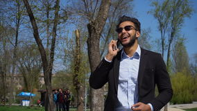 Arabian talking online with travel agent. Young man holds in hand phone and talking. Arabian has dimples on cheeks, dark hair and beard. Guy wears black jacket stock video