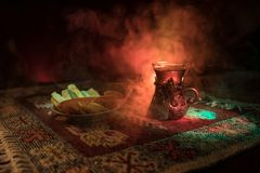 Arabian tea in glass with eastern snacks on a carpet on dark background with lights and smoke. Eastern tea concept. Empty space. Stock Images