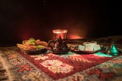 Arabian tea in glass with eastern snacks on a carpet on dark background with lights and smoke. Eastern tea concept. Empty space. Royalty Free Stock Photography