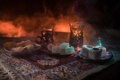 Arabian tea in glass with eastern snacks on a carpet on dark background with lights and smoke. Eastern tea concept. Empty space. Royalty Free Stock Photos