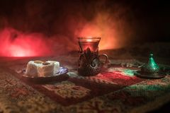 Arabian tea in glass with eastern snacks on a carpet on dark background with lights and smoke. Eastern tea concept. Empty space. Stock Photo