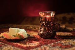 Arabian tea in glass with eastern snacks on a carpet on dark background with lights and smoke. Eastern tea concept. Empty space. Stock Photography