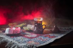 Arabian tea in glass with eastern snacks on a carpet on dark background with lights and smoke. Eastern tea concept. Empty space. Stock Photos