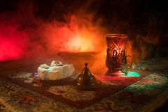 Arabian tea in glass with eastern snacks on a carpet on dark background with lights and smoke. Eastern tea concept. Empty space. Royalty Free Stock Photo