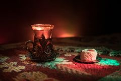 Arabian tea in glass with eastern snacks on a carpet on dark background with lights and smoke. Eastern tea concept. Empty space. Royalty Free Stock Image