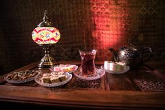 Free Arabian Tea In Glass With Eastern Snacks On Vintage Wooden Surface. Eastern Tea Concept. Low Light Lounge Interior With Carpet. Stock Photography - 138973802