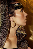 Arabian woman brunette in ethnic accessories, shawl hijab. Gold make-up. Stock Photography