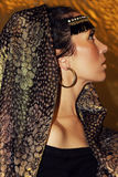 Arabian woman brunette in ethnic accessories, shawl hijab. Gold make-up. Stock Photos