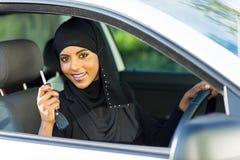 Arabian woman car key. Happy arabian woman holding car key inside new vehicle Royalty Free Stock Image