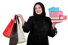 Arabian woman carrying shopping bags and gift boxes isolated on white Royalty Free Stock Images