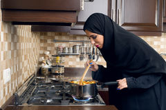 Arabian woman cooking stew in the kitchen.  Royalty Free Stock Images