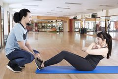 Arabian woman doing sit ups with her trainer. Picture of Arabian women doing sit ups with her trainer. Shot in the fitness center Royalty Free Stock Photography