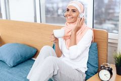 An Arabian woman is drinking tea and listening to music while sitting on the bed. She rests at home Royalty Free Stock Images