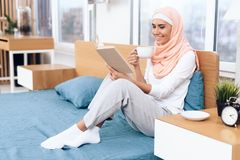 An arabian woman is drinking tea and reading a book while sitting on the bed. She rests at home Stock Photography