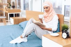 An arabian woman is drinking tea and reading a book while sitting on the bed. She rests at home Royalty Free Stock Images
