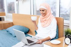 An arabian woman is drinking tea and working on the computer while sitting on the bed. She rests at home Royalty Free Stock Image