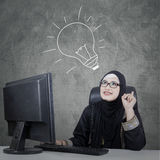 Arabian woman with hand drawn lightbulb. Arabian businesswoman sitting in front of computer and thingking of ideas with hand drawn lightbulb Stock Photos