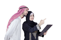 Arabian woman and her partner look at something. Photo of Arabian businesswoman and her partner holding a clipboard while pointing and looking at something Royalty Free Stock Image