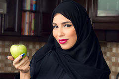 Arabian woman holding an apple in the kitchen. Fitness concept Stock Photos