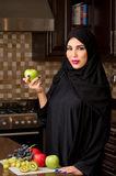 Arabian woman holding an apple in the kitchen Stock Images