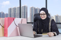 Arabian woman with laptop and shopping bags. Picture of happy Arabian woman shopping online by using credit card and laptop with shopping bags on desk Royalty Free Stock Photos