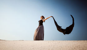 Arabian woman with long cloth at desert on windy day Stock Images