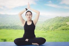 Arabian woman meditating in the meadow stock image