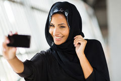 Arabian woman self portrait. Happy arabian woman taking self portrait using cell phone Royalty Free Stock Photo