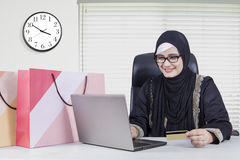 Arabian woman shopping online. Photo of Arabian young woman holding credit card and shopping online with laptop Stock Photo