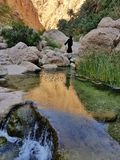 Arabian woman in the stone valley walking near clear water and waterfall stock image