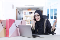 Arabian woman talking on cellphone. Picture of Arabian young woman shopping online and talking on the phone with laptop on the table Royalty Free Stock Photo