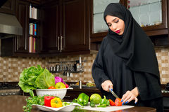 Arabian woman wearing hijab cutting veggies in the kitchen