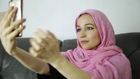 Arabian woman wearing a hijab in video chat with her friends on a mobile phone.  stock footage