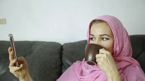 Arabian woman wearing a hijab in video chat with her friends on a mobile phone.  stock video footage