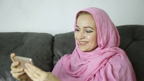 Arabian woman wearing a hijab in video chat with her friends on a mobile phone.  stock video